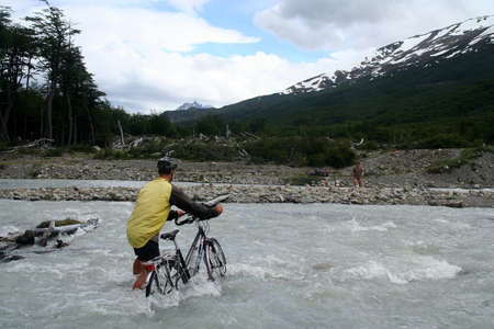 Cyclist crossing the river during journey from Villa O�Higgins in Chile to argentinian border at Lago Desierto � crossing one of the most remote borders in the world photo
