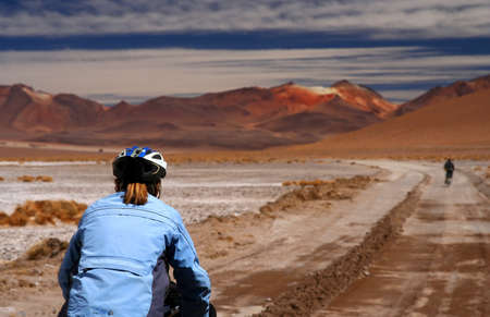 Lonely cyclist on the sandy road in Altiplano in Bolivia photo