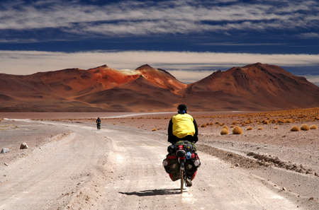 Lonely cyclist on the sandy road in Altiplano in Bolivia 免版税图像