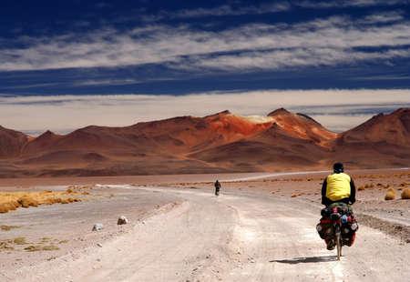 Eenzame fietser op de zandweg in Altiplano in Bolivia