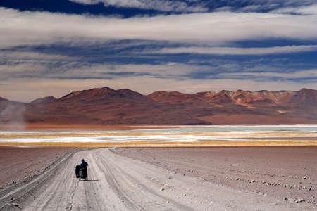Girl struggling with her bike on a sandy track in Altiplano, Bolivia Foto de archivo