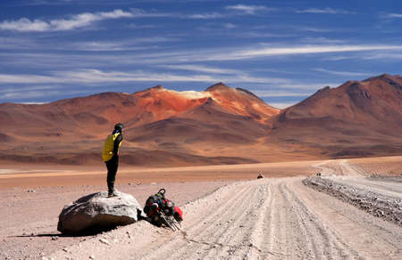 endeavor: cyclist taking break on the rock on the road in Altiplano in Bolivia