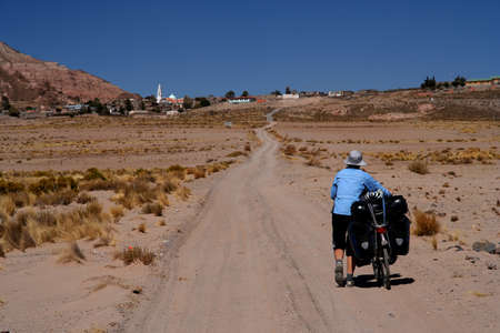 Lonely cyclist travelling through the remote, rural bolivian countryside photo