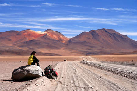 Lonely cyclist taking break on the rock on the sandy road in Altiplano in Bolivia Standard-Bild