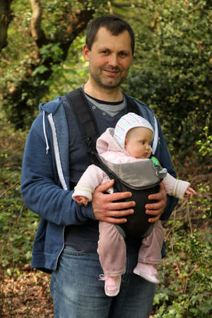 Father carrying his daughter in a baby carrier photo