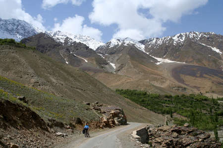 Woman cycling on a difficult mountain road towards Shandur Pass in northern Pakistan photo