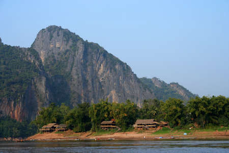 Small lao village on the banks of Mekong river photo