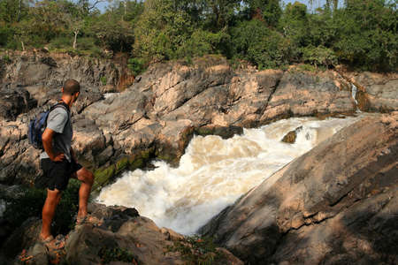 Tourist admiring powerful Don Khon  Khon Phapheng   waterfall on the Mekong river, Don Det, Laos Stock Photo - 16085380