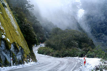Steep icy mountain road in winter leading to Haast Pass in New Zealand photo