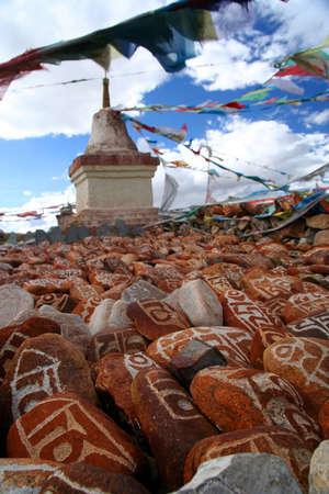 mantra: Mani stones   Marnyi Stones with OM MA  325;I PADME HUM -  six syllabled mantra of Tibetan Buddhism engraved on them   -  and Buddhist stupa located at the Ji Wu Monastery near Lake Manasarowar, Tibet