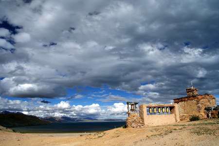 Small old Tibetan monastery and praying mills on a hill above holy Lake Manansovar, Tibet Stock Photo - 16777114