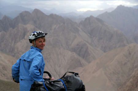 Single female cyclist on the bicycle on the remote road in Eastern Tibet photo
