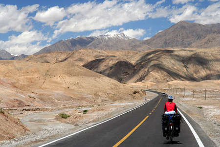 Single female cyclist on the bicycle cycling on the Karakorum Highway in China Imagens
