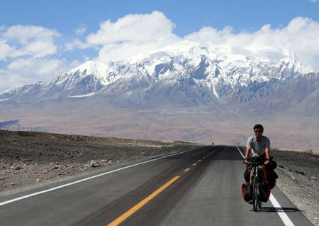 Single male cyclist on the bicycle cycling on the Karakorum Highway in China photo