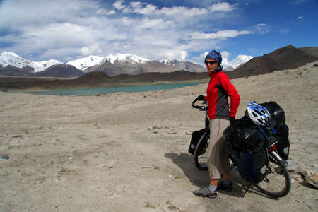 Single female cyclist on the bicycle on the remote road in Eastern Tibet Stock Photo - 16942090