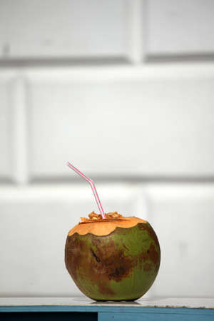 Open coconut with a straw to drink liquid from inside Stock Photo - 17344275