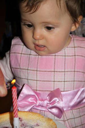 blow out: Bambina che prova a spegnere la prima candelina su una prima torta di compleanno Archivio Fotografico