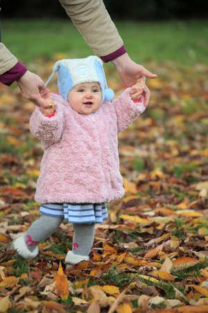 bambini pensierosi: Madre con la sua piccola figlia in una passeggiata in un parco in autunno
