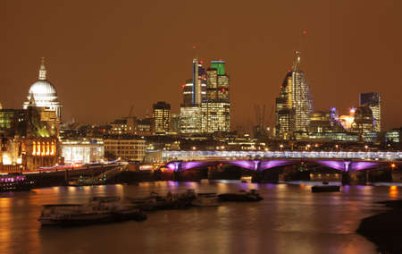 Night skyline of London with St  Pauls cathedral and commercial buildings as seen from the Waterloo bridge