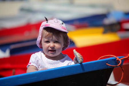 Cute little girl standing in front of a boat in port in La Gomera island in Canary Islands, Spain photo