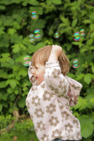 mesmerized: Young little girl running after little soap bubbles