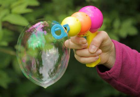liquid soap: Plastic toy gun to make soap bubbles Stock Photo