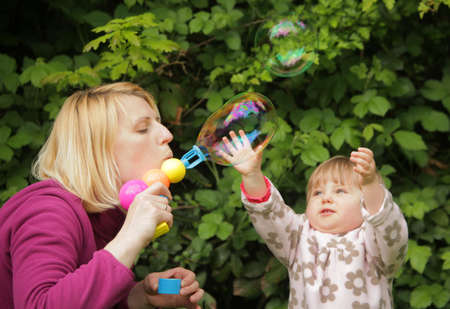 Mother and daughter having fun with soap bubbles photo