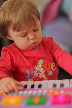 Baby girl playing her toy piano at home photo
