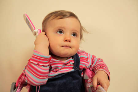 Baby girl pretending to call home on her toy mobile phone photo