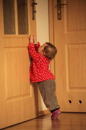 Baby meisje proberen om een deurklink bereiken om eruit te komen van de kamer Stockfoto