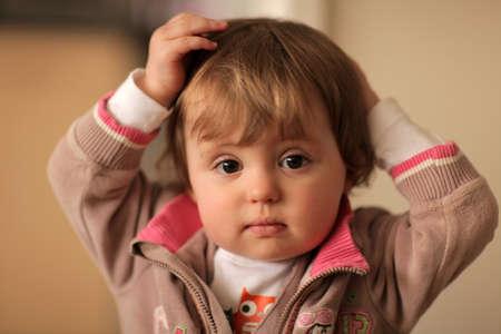 Mischevious Baby Mädchen, das sie etwas falsch gemacht haben weiß aber vorgibt, sie tat es nicht - es ist einfach passiert Standard-Bild - 20077725