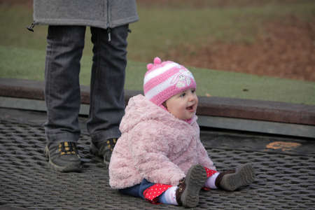 Little cute baby girl sitting on a trampoline in the park playground photo