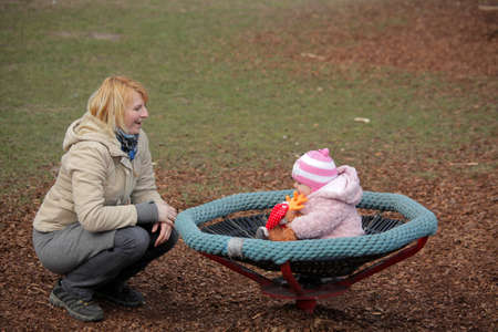 Little cute baby girl sitting on a small carousel in the park playground photo