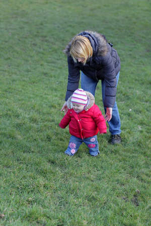 Baby girl and her mother walking on the grass in the park photo