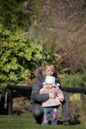 Portrait of a baby girl and her mother in the park photo
