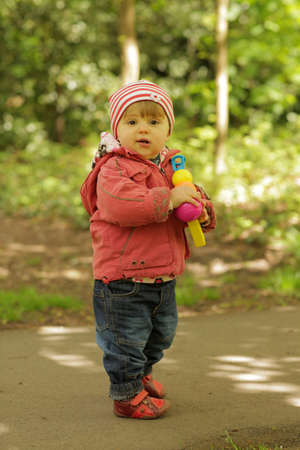 Baby girl standing on the ground in the garden in spring holding plastic toy soap bubbles gun photo