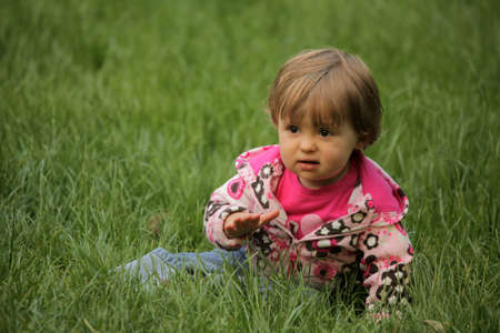 Baby girl sitting on the grass in the garden in spring photo