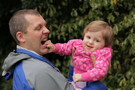 Father holding his daughter during day out in the park photo