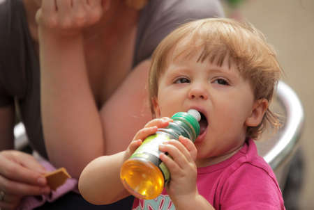 Baby girl drinking juice from a plastic bottle on a hot summer day photo