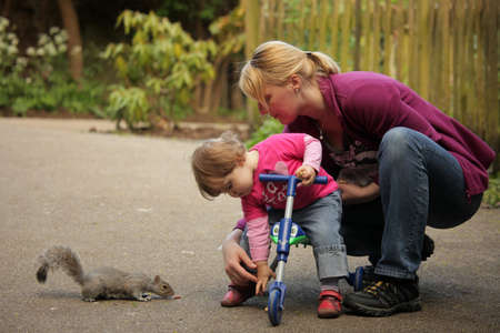Mother and daughter feeding squirrels in the park photo