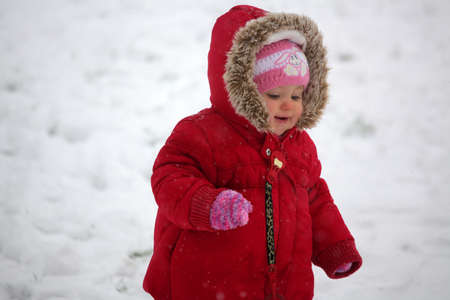 Baby girl walking in the snow in the park on a cold winter day photo