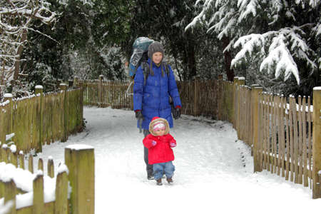 Woman with her baby in the carrier during walk to the park on a cold winter day photo
