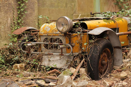 Old forgotten car rusting at the backyard of an old english property