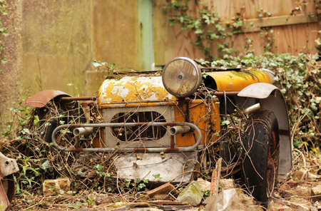 Old forgotten car rusting at the backyard of an old english property photo