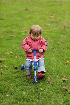 Little girl riding on her tricycle on a pathway in a park in spring
