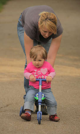Cute baby girl sitting on her trike being pushed by her mother photo