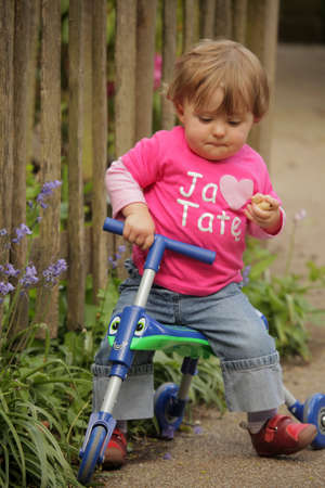 Little girl riding on her tricycle on a pathway in a park in spring Stock Photo - 20197635