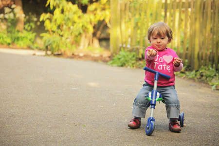 Little girl riding on her tricycle on a pathway in a park in spring photo
