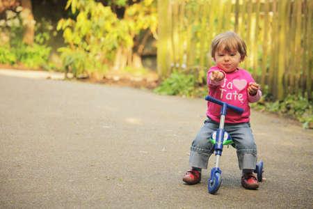 Meisje rijdt op haar driewieler op een pad in een park in het voorjaar