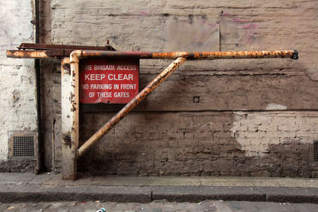 Old rusted barrier with a KEEP CLEAR sign and information that this road will be used for evacuation in an emergency, London Standard-Bild